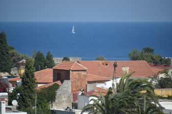 Greece-Rhodes-Rhodes old town-roofs-sea-blue-sailing boat