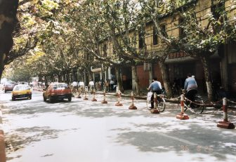 China-Kunming-street-a row of trees-cars-people