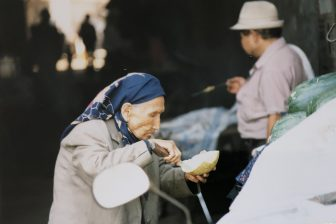 China-Urumchi-Tian Chi Lu market-an old woman-melon-eating
