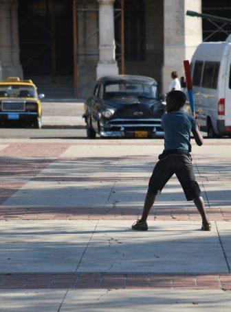 a boy holding a bat at Centro Habana