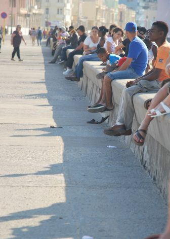 many people sitting on the wall along Malecon
