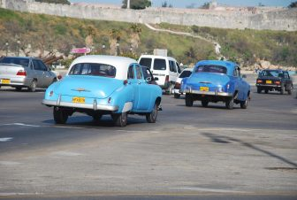 two blue classic cars running on the road in Havana