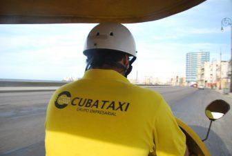 黄色い服のココタクシーの運転手