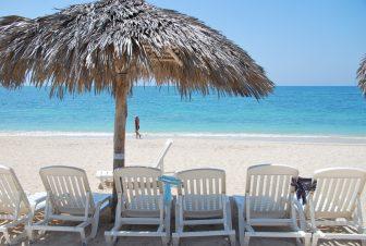 キューバ南部のアンコン・ビーチのデッキチェアとパラソル
