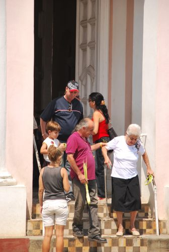 people coming out of the pink church after the mass in Rodas, Cuba