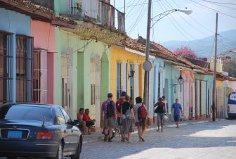 the colourful houses along the road with people in Trinidad in Cuba