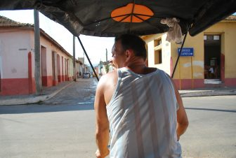 the back of the driver of a bicycle taxi running on the road in Trinidad in Cuba