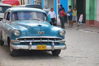キューバのトリニダの通りに停まっていたクラシックカーと生活する人々