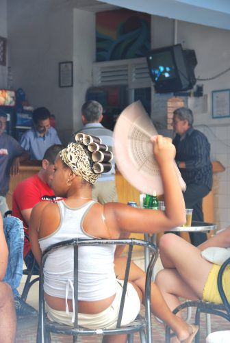 a woman cooling herself with a fan at a cafe in Trinidad, Cuba