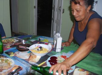 a woman serving foods on the table in her house in Trinidad, Cuba